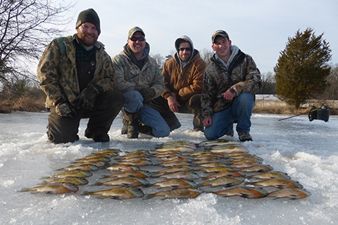 A group of ice fishermen pose behind their catch for the day.