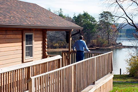 A man enjoys a view of the lake from the porch of a log cabin at Yellow Creek State Park.