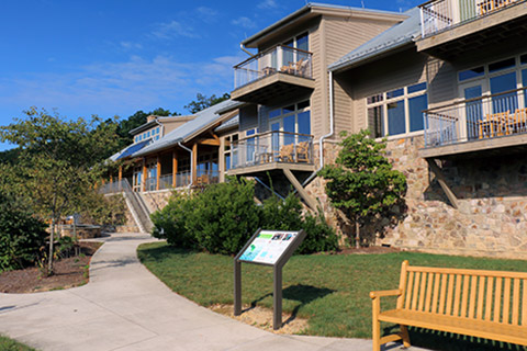 A bench and an exhibit are in front of a hotel with many porches which is the Nature Inn at Bald Eagle State Park.