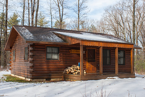 A modern log cabin in in snow at Black Moshannon State Park.