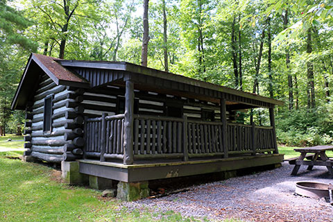 A log cabin with a porch is in the forest at Black Moshannon State Park.