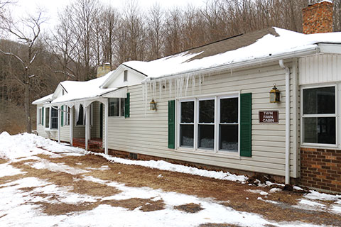 A house is covered in snow and icicles at Blue Knob State Park.