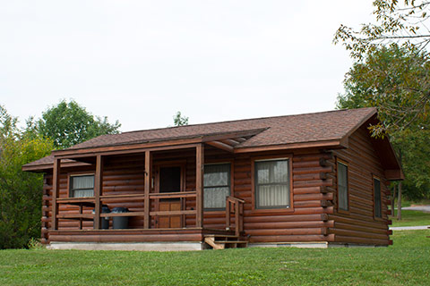 A modern log cabin is near trees at Canoe Creek State Park.
