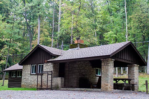 A wood and stone cabin is near the forest at Clear Creek State Park.