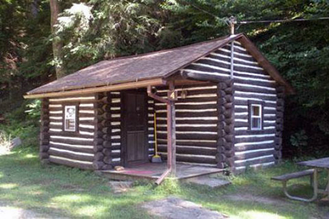 A log cabin is near the forest at Cook Forest State Park.