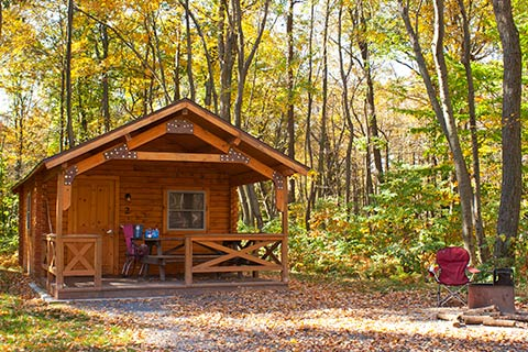 A cozy log cabin is in the forest at French Creek State Park.