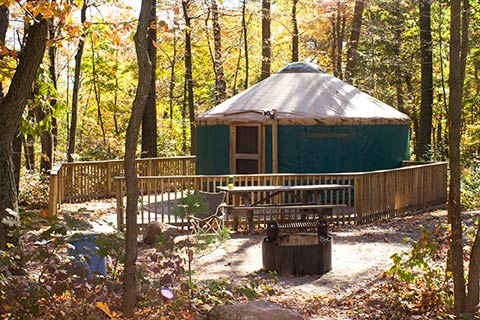 A round tent with a wooden floor is in the forest at French Creek State Park.