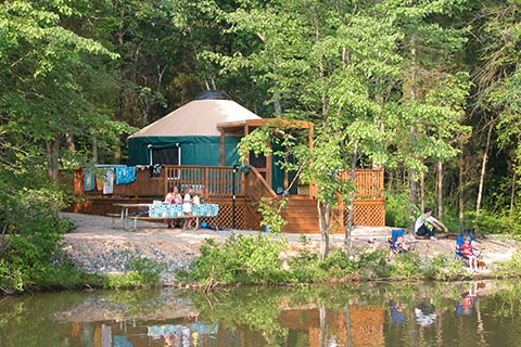A family enjoys a round tent with a porch is near the lake at Gifford Pinchot State Park.