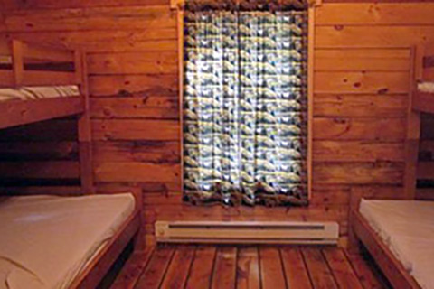 Bunk beds, electric heat, and a window are part of the interior of a deluxe camping cottage at Hickory Run State Park.