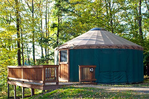A round, canvas tent with a wooden proch is near trees at Hills Creek State Park.