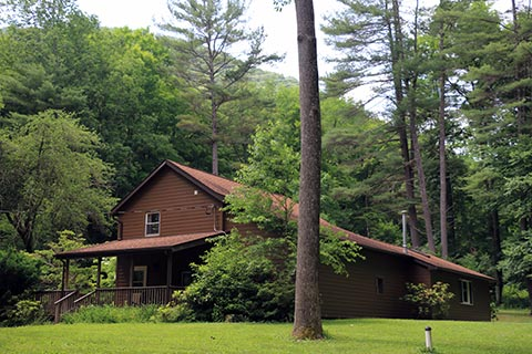 A modern cabin is by forest at Hyner Run State Park.