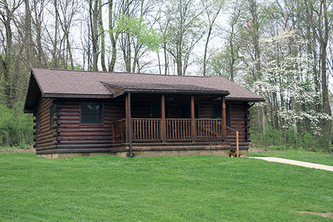 A Modern Log Cabin Is Near Trees At Keystone State Park.