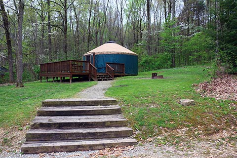 Up a flight os steps is a round tent with a wooden porch at Keystone State Park.