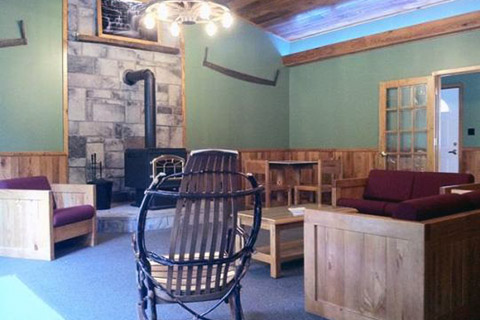 Wood furniture, a wood stove, and wood wainscotting highlight the interior of the Copper Kettle Lodge at Laurel Hill State Park.