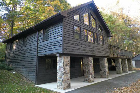 An impressive wainy wood sided building with large windows and a porch is in the forest at Laurel Hill State Park.