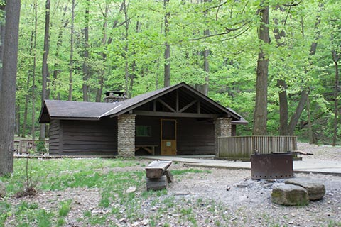 A modern, wainy-wood cabin is near trees at Linn Run State Park.