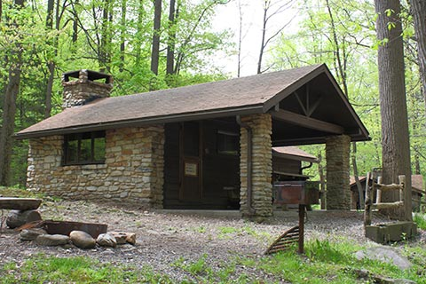 A rustic, stone cabin is surrounded by trees at Linn Run State Park.