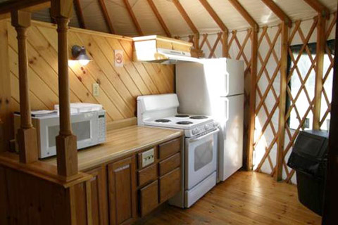 A counter, microwave oven, stove, and refrigerator are in a wooden room in a yurt at Little Pine State Park.