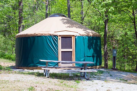 A round tent with a door is near a forest at Ohiopyle State Park.