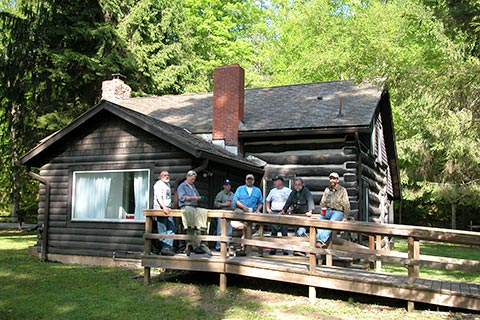 People enjoy a log cabin at Ole Bull State Park.