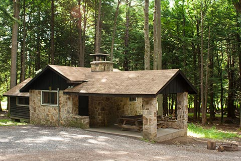 A stone, rustc cabin is in the forest at Parker Dam State Park.