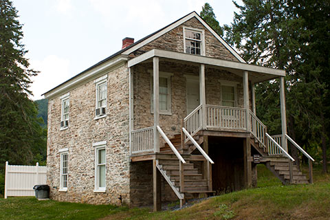 A historic, stone house has multiple staircases and a small porch at Pine Grove Furnace State Park.