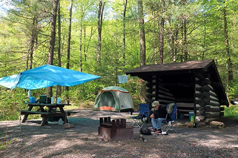 A camper sits by a campfire in front of a tent and an Adirondack shelter at Poe Paddy State Park.