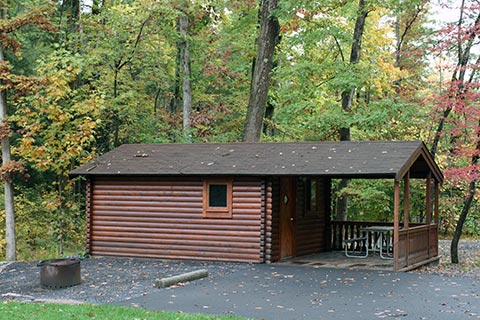 A cozy log cabin is near trees at Poe Valley State Park.