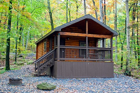 A cozy log cabin is surrounded by a forest at Poe Valley State Park.