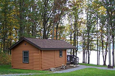 A cozy log cabin has a lake view at Prince Gallitzin State Park.
