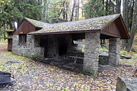 A cozy stone, rustic cabin is dappled with autumn-colored leaves at Promised Land State Park.