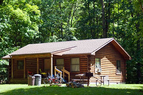 Bikes are in front of a modern log cabin at Pymatuning State Park.
