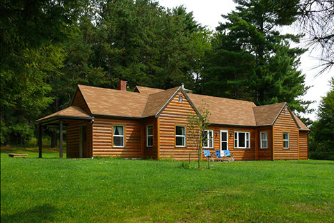 A very large log cabin is near the forest at Raccoon Creek State Park.