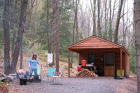 A camper enjoys a campfire outside of a cozy log cabin at Raymond B Winter State Park.