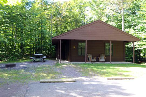 A modern log cabin is near a forest at Ricketts Glen State Park.