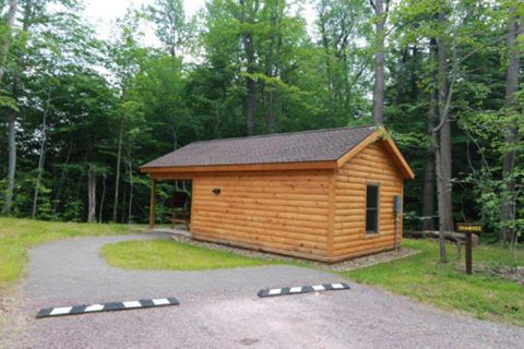A cozy log cabin is near a forest at Ricketts Glen State Park.