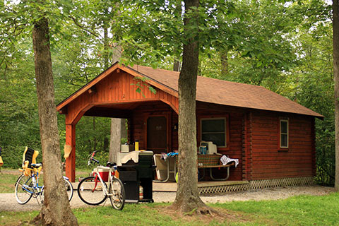 Bikes and a grill sit in front of a cozy log cabin at Shawnee State Park.