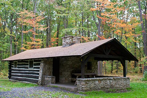A cozy log and stone cabin is near a forest just starting to turn autumn-colored at Simon B Elliott State Park.