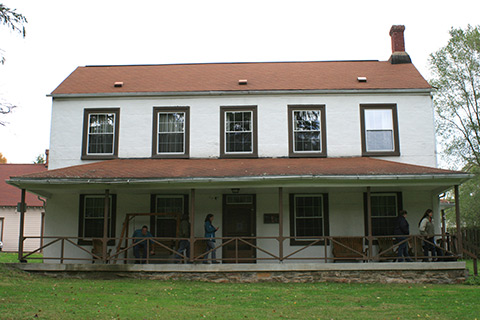 People enjoy a porch on a large, historic building at Trough Creek State Park.