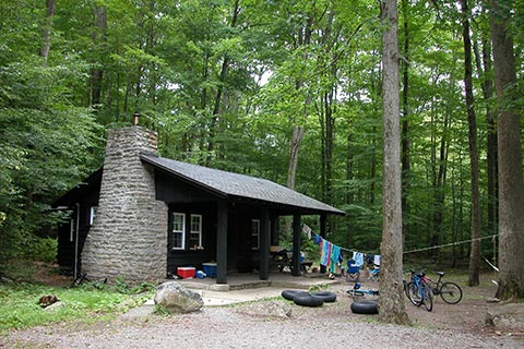 Drying clothes, inner tubes, and parked bikes are near a quaint rustc cabin surrounded by trees at Worlds End State Park.
