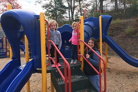 A family poses on new playground equipment at a community park.