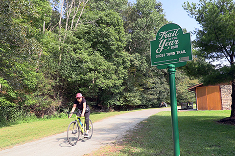 A person rides a bike passed a metal sign reading: Trail of the Year Ghost Town Trail