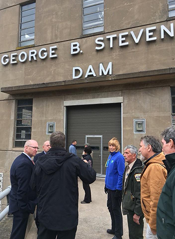 DCNR Secretary Dunn and others stand in front of the restored George B. Stevenson Dam