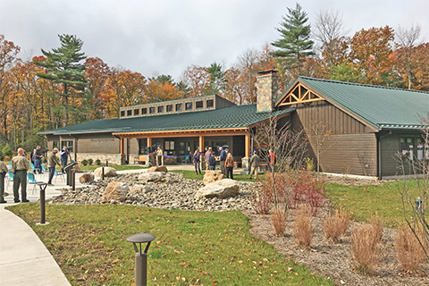People stand and walk around the Hickory Run Visitor center with trees and plants around the building